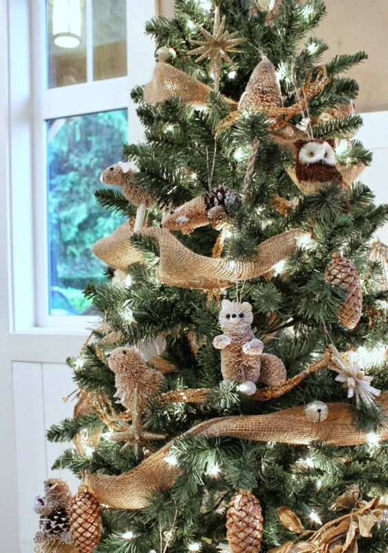 fake animal ornaments, gilded pinecones, jingle bells and burlap ribbons bring a strong rustic feel to the tree