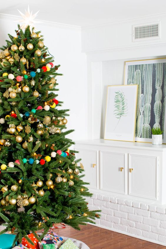 gold ornaments and a colorful pompom garland over the tree is a fun and whimsy idea for Christmas