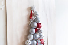 17 take a plywood sheet and attach some Christmas ornaments to it forming a Christmas tree and hang it on the wall