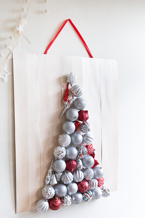 take a plywood sheet and attach some Christmas ornaments to it forming a Christmas tree and hang it on the wall