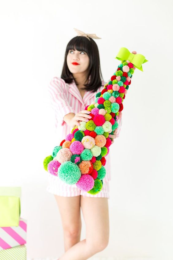 a bright and colorful pompom Christmas tree with a neon bow on top is a gorgeous idea for those who love colors