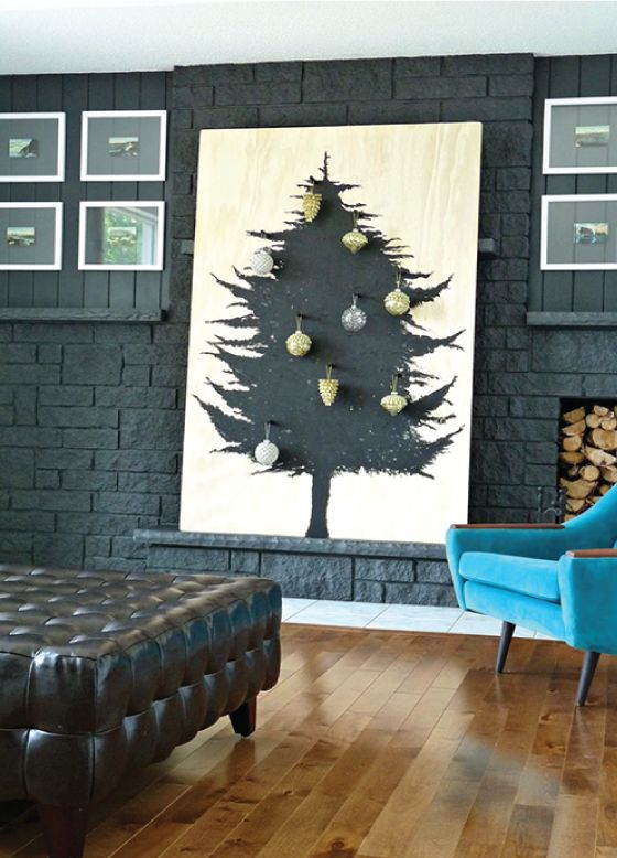 a plywood sheet with a Christmas tree painted in black on it and some ornaments attached