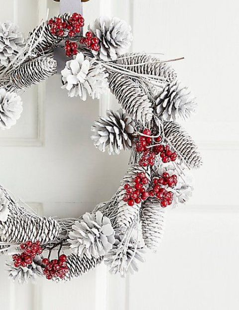 a snowy Christmas wreath of vine, pinecones and fake red berries that add color to it
