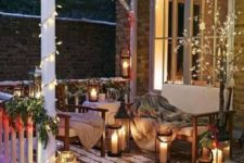 18 a sofa and a chair with faux fur blankets, candle lanterns, greenery and berry garlands on the railings