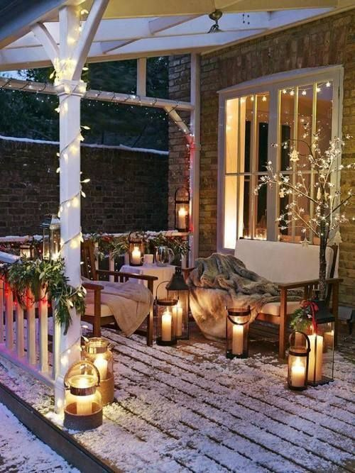 a sofa and a chair with faux fur blankets, candle lanterns, greenery and berry garlands on the railings