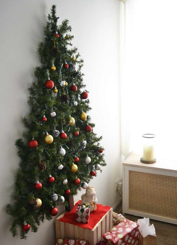 a wall mounted Christmas tree made of evergreen branches and decorated with snowy pinecones and ornaments