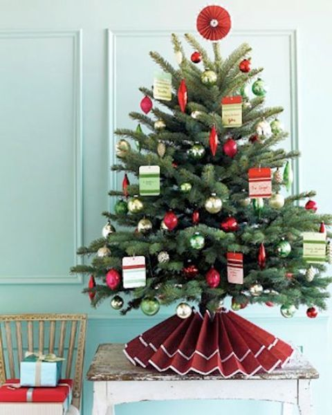 a Christmas tree decorated with silver, green and red ornaments, with Christmas cards and a paper skirt