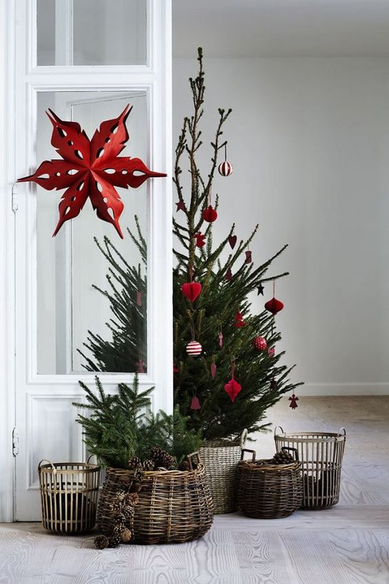 a Scandinavian Christmas tree between modern and traditional with red and white ornaments and baskets around