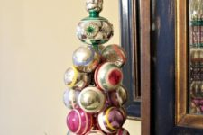 19 a cool vintage Christmas ornament tree placed on evergreens is a cool decoration for a shelf or a mantel