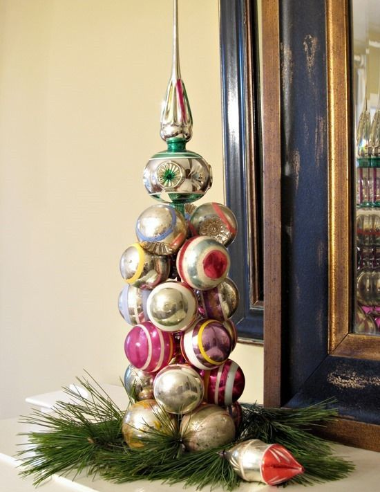 a cool vintage Christmas ornament tree placed on evergreens is a cool decoration for a shelf or a mantel