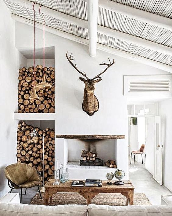 a fireplace and firewood storage by its side for a modern yet rustic space, a sisal rug and whitewashed wood
