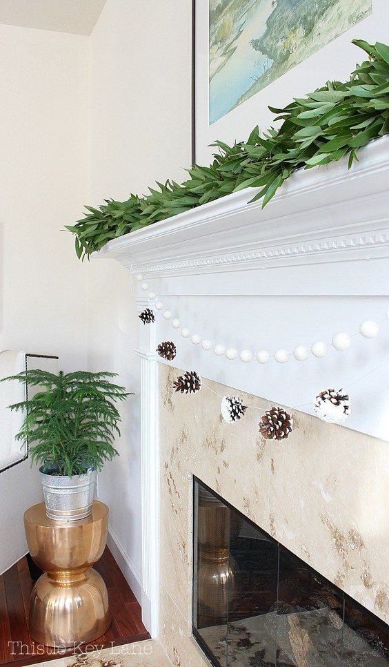 a snowy pinecone and pompom garland is great for decorating a fireplace, add a fresh greenery garland on top
