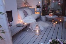 19 a super cozy winter terrace with a built-in fireplace, a bench, lights, candles, lanterns, potted flowers