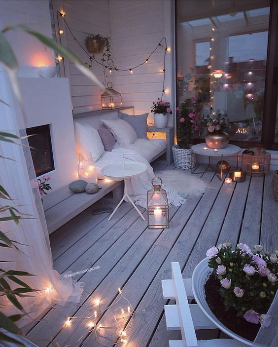 a super cozy winter terrace with a built-in fireplace, a bench, lights, candles, lanterns, potted flowers