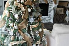 20 a chic and shiny Christmas tree with burlap ribbons, pompom garlands, snowflakes, white and silver ornaments and pinecones