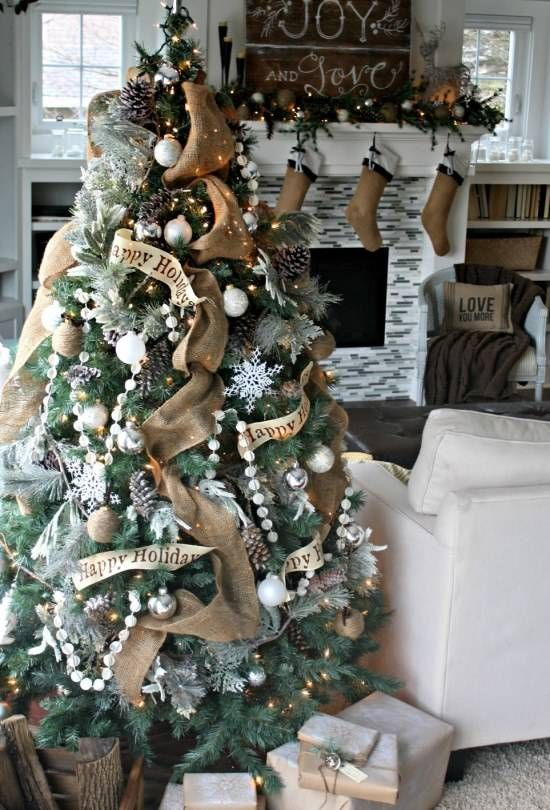 a chic and shiny Christmas tree with burlap ribbons, pompom garlands, snowflakes, white and silver ornaments and pinecones