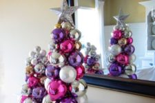 20 a duo of tabletop Christmas trees of colorful Christmas ornaments glued to each other with a silver star on top