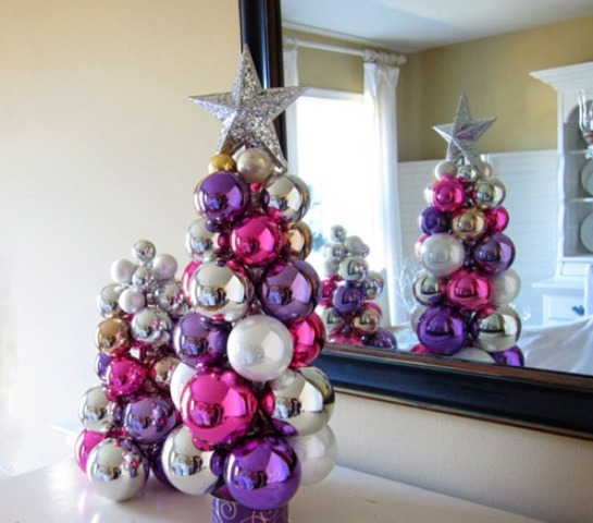 a duo of tabletop Christmas trees of colorful Christmas ornaments glued to each other with a silver star on top