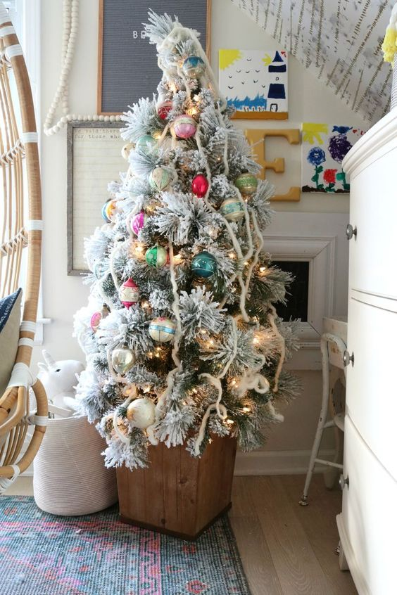 a flocked Christmas tree in a wooden box and decorated with colorful ornaments with a vintage feel