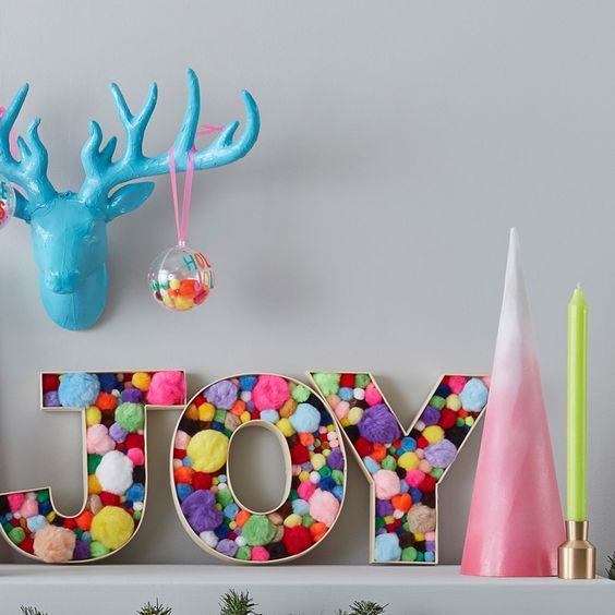a fun and colorful Christmas decoration of letters filled with colorful pompoms of various sizes