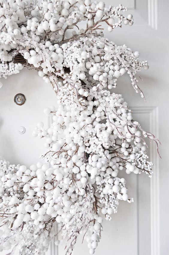 a gorgeous snowy Christmas wreath of fake white berries and pompoms will create a chic frozen winter look anywhere