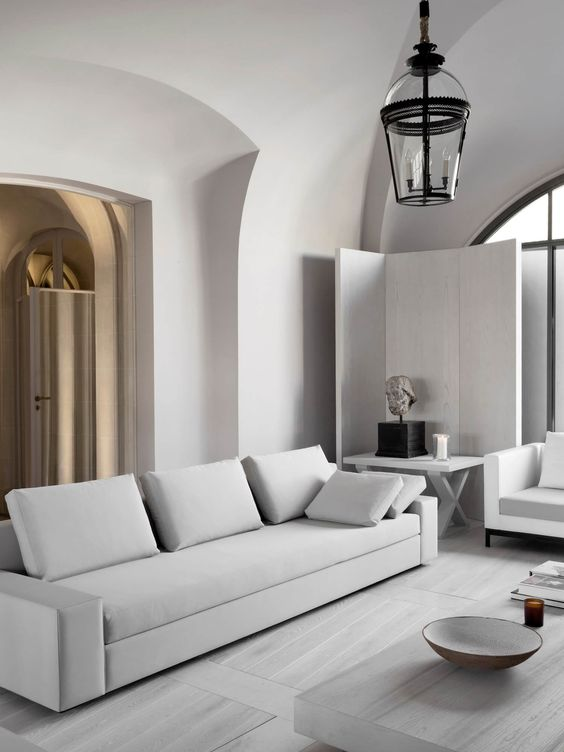 a neutral minimalist living room with clean lined furniture and an accent lamp mixing modern and vintage