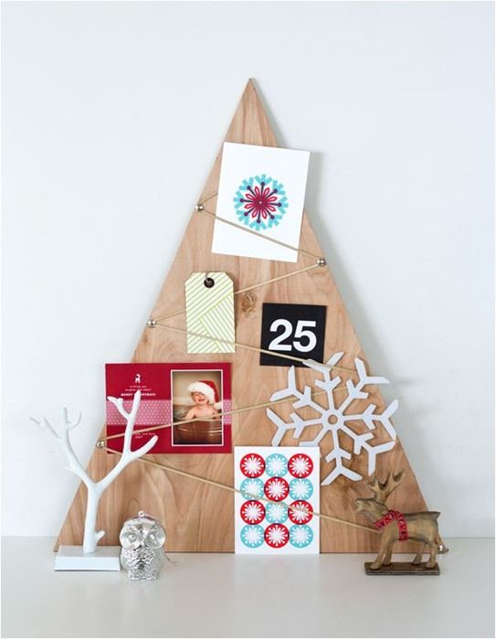 a simple tabletop Christmas tree decorated with Christmas cards and snowflakes plus gift tags for a modern space