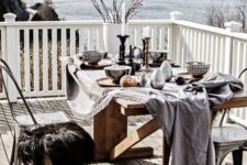 20 a winter terrace with a dining zone, a wooden table and mismatching chairs covered with faux fur