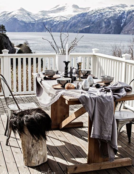 a winter terrace with a dining zone, a wooden table and mismatching chairs covered with faux fur