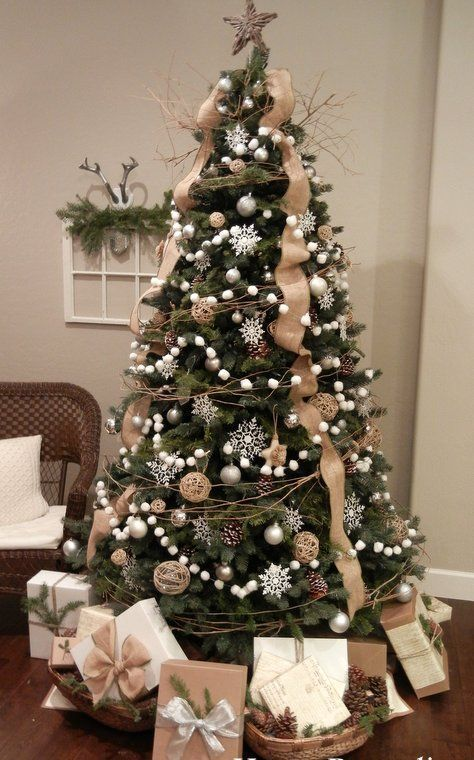 a chic Christmas tree with white snowflakes, ball ornaments, twigs, pompomg garlands, burlap ribbons and vine ornaments