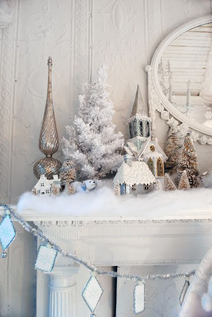 a mantel covered with cotton as fake snow and with a flocked mini tree and snowy trees and houses