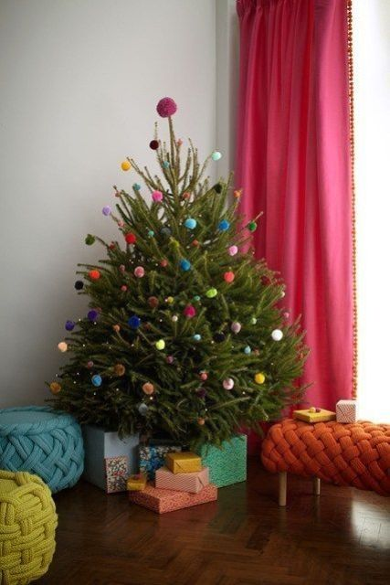 a small Christmas tree decorated only with colorful pompoms and LEDs is a fun and whimsy idea