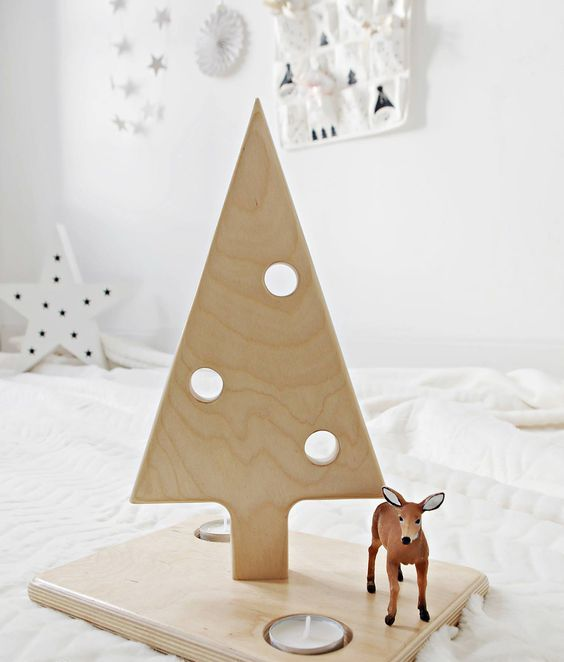 a small plywood Christmas tree on a stand with holes imitating ornaments and some candles