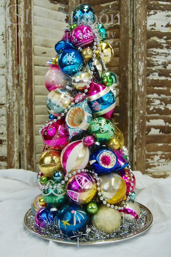 a super colorful and vintage Christmas tree made of ornaments and beads on a tray is a creative idea