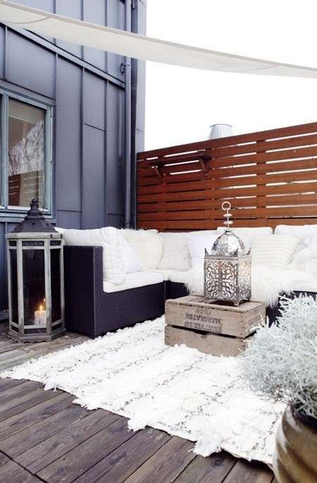 a winter terrace with a fur rug, pillows and fluffy throws, a crate with a decorative lantern and candle lantern