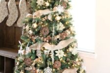 22 a chic rustic Christmas tree with vine and snowflake ornaments, pinecones, lights and lots of burlap plus a burlap bow on top
