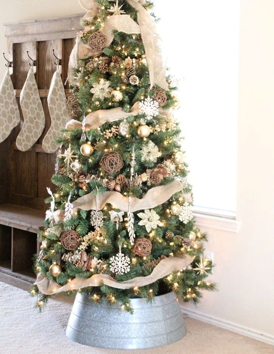 a chic rustic Christmas tree with vine and snowflake ornaments, pinecones, lights and lots of burlap plus a burlap bow on top