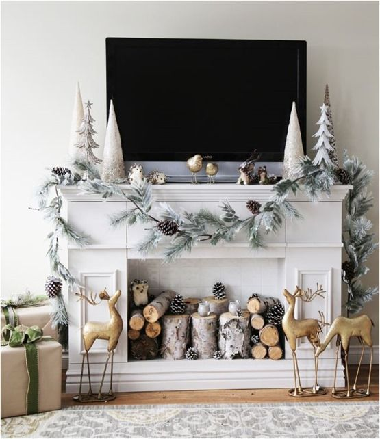 a mantel decorated with a snowy evergreens and snowy pinecones garland for a real winter feel