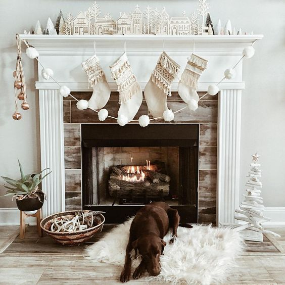 a mantel styled with metallic jingle bells and a white pompom garland for Christmas