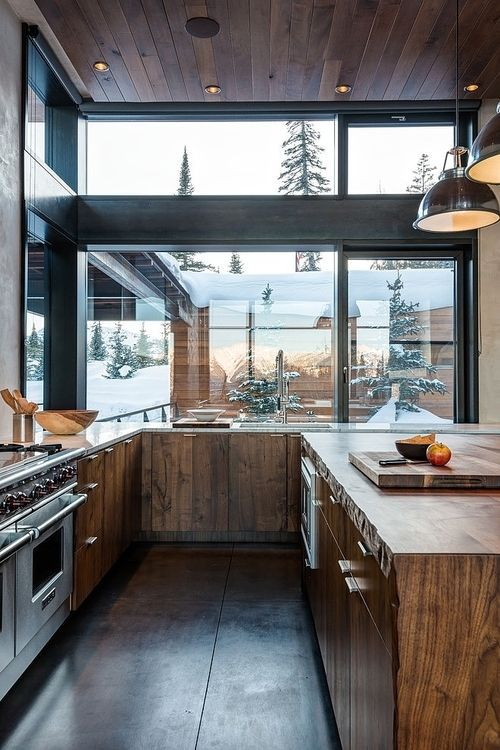 a modern rustic kitchen with stained wooden cabinets, ceiling and floor is a fine example of the style