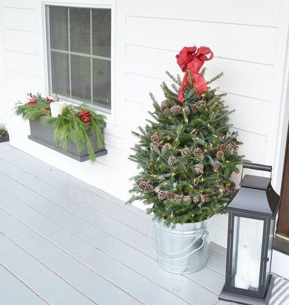 a small holiday tree decorated with lights, pinecones and a red bow on top in a galvanized bucket for a porch