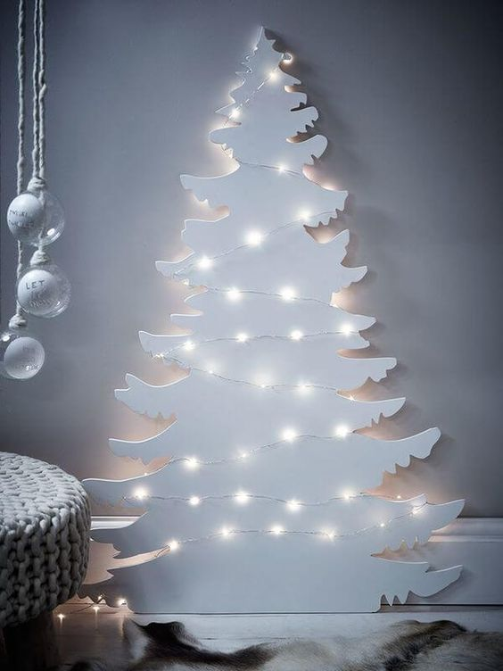 a white plywood Christmas tree decorated with lights instantly creates a winter wonderland feel in your home