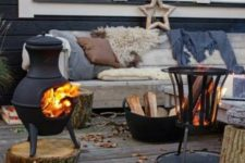 22 a wooden bench softened with blankets, pillows and faux fur, two fire bowls and firewood in a bucket for a Scandi feel