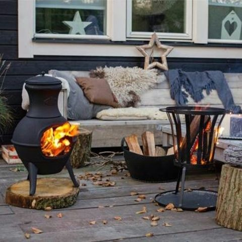 a wooden bench softened with blankets, pillows and faux fur, two fire bowls and firewood in a bucket for a Scandi feel