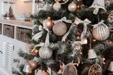 23 a glam rustic Christmas tree decorated with wicker bells, wooden and metal ornaments and some ball ornaments and pinecones