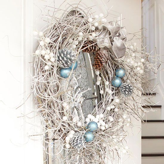 a snowy and messy holidya wreath with vines, pinecones, fake berries, ornaments and a ribbon bow