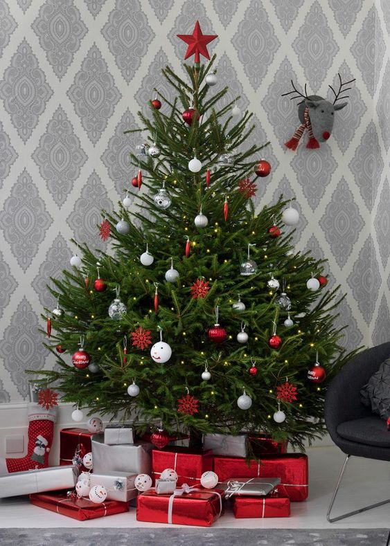 a traditional Nordic Christmas tree with white, silver, clear and red ornaments and a red star on top