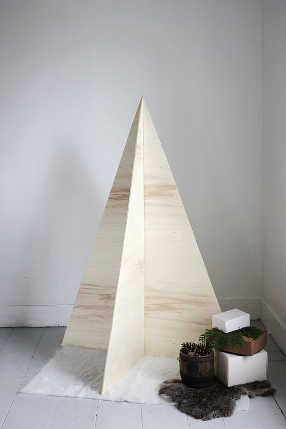 an ultra minimalist Christmas tree of plywood with no decor, just some gifts and faux fur