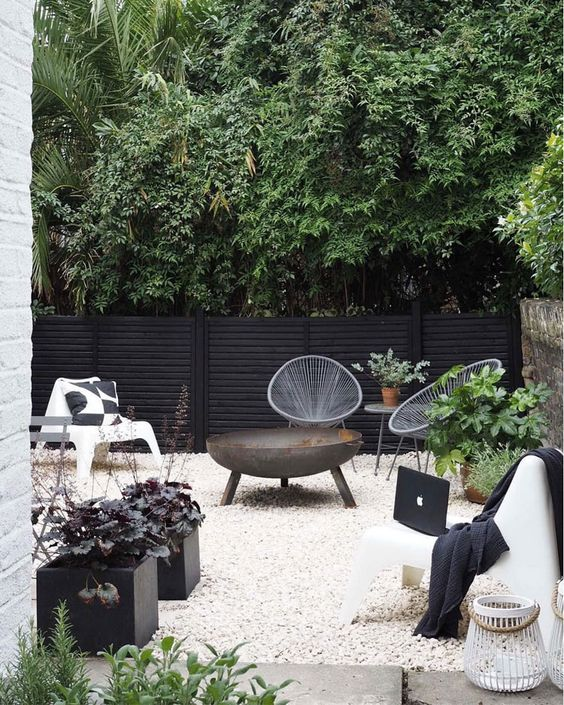 a Scandinavian terrace in black and white, with potted greenery and a fire bowl