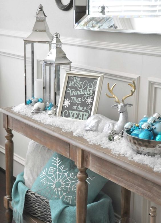 a snowy console with fake snow, ornaments, lanterns, signs and a fake deer for a cozy and cool Christmas look